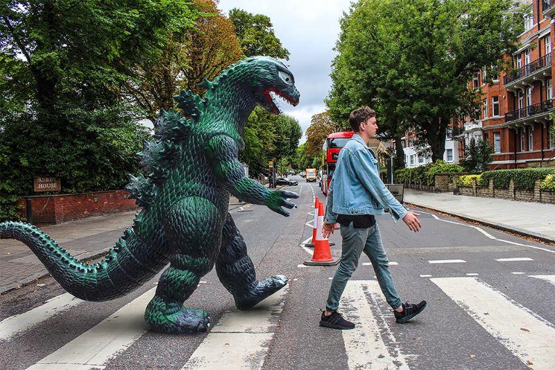 Парень путешествует с гигантской пластиковой Годзиллой